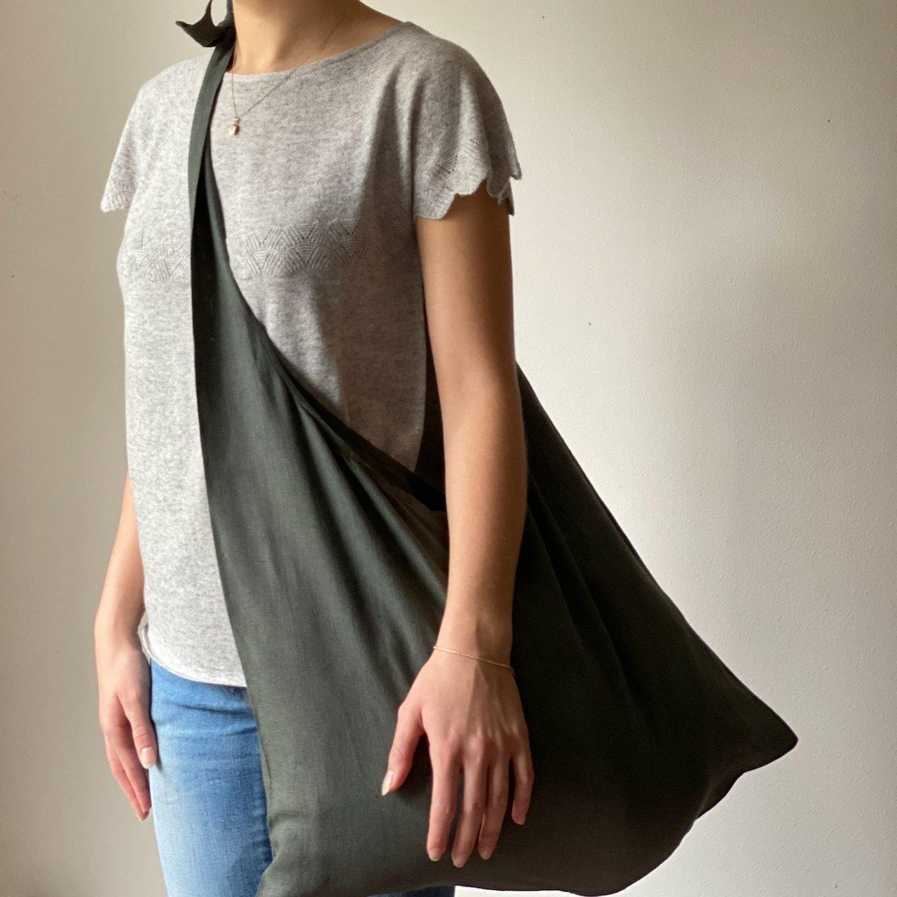 Model showing Hang Bag in Khaki Green by Care By Me. Minimalist design, Japanese-inspired, simple knot to adjust strap length. 100% GOTS Linen.