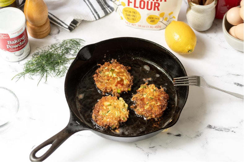 Hot cast iron pan with sizzling Zucchini patties frying.
