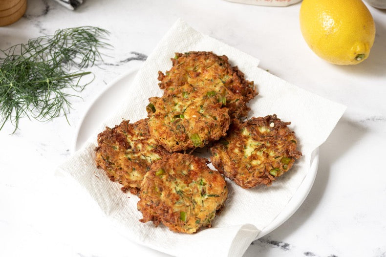 Crispy Zucchini patties resting on a paper towel in a stack
