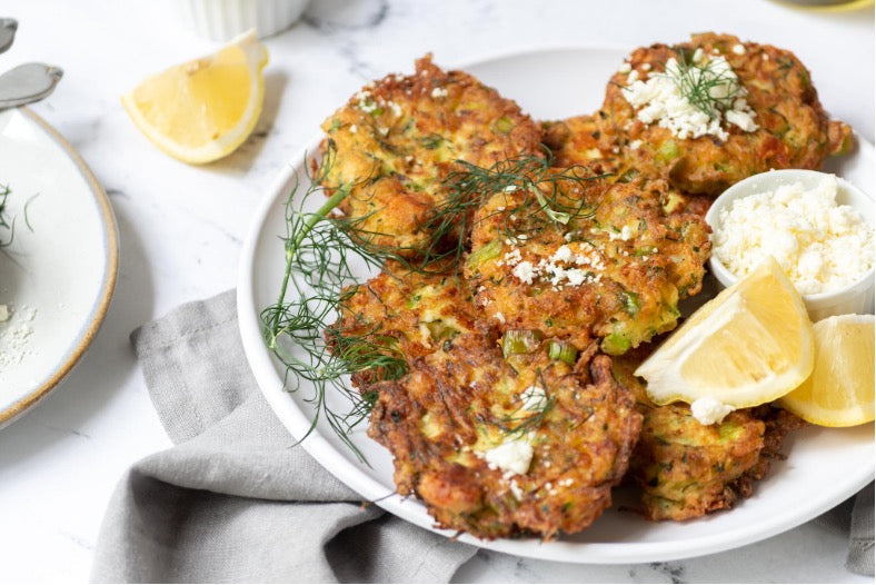 Zucchini patties plated beautifully with a side of lemon wedges and feta cheese.