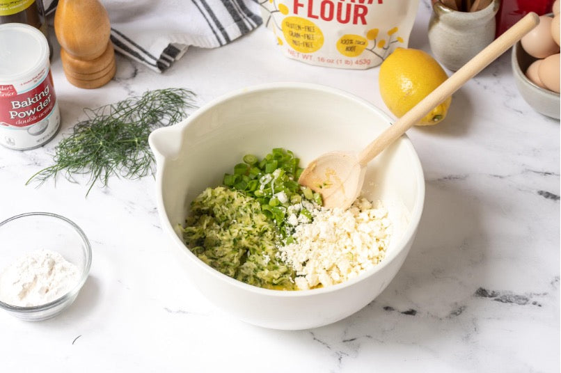 Mixing bowl with Zucchini, scallions, dill, feta, garlic, and pepper