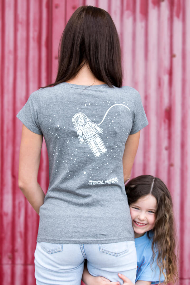 back view of a dark haired woman wearing a mid heather grey screen printed t-shirt with child against a red background