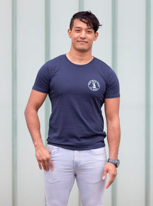 man wearing a navy blue screen printed t-shirt against blue background