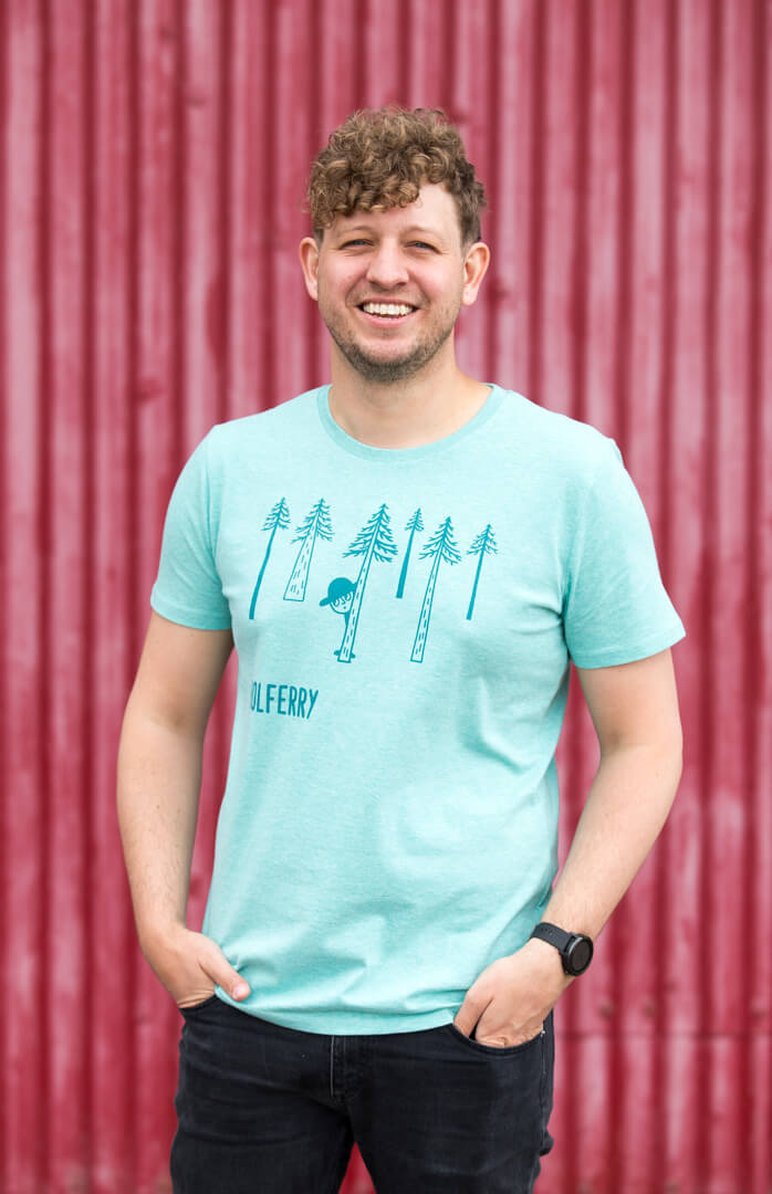 man wearing a heather green screen printed t-shirt against red background