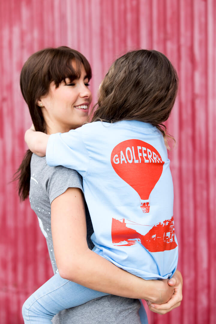 back view of a brown haired girl wearing a sky blue screen printed t-shirt against red background