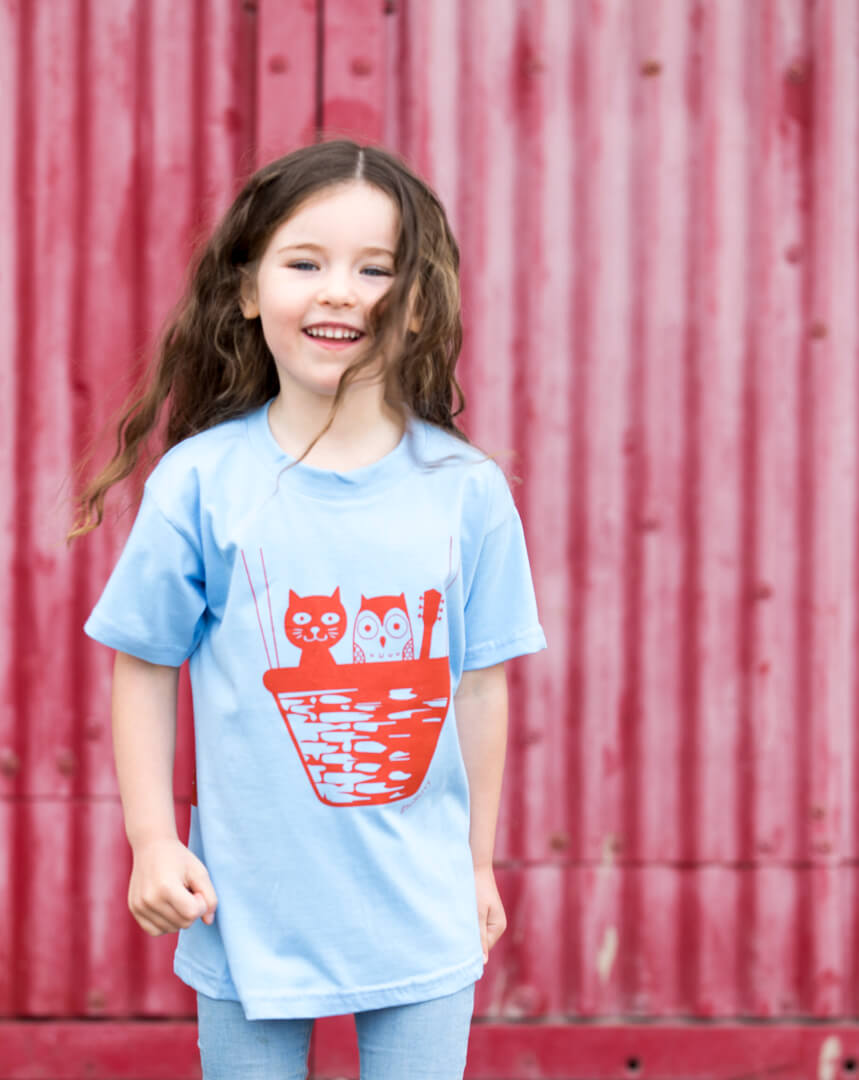 brown haired girl wearing a sky blue screen printed t-shirt against red background