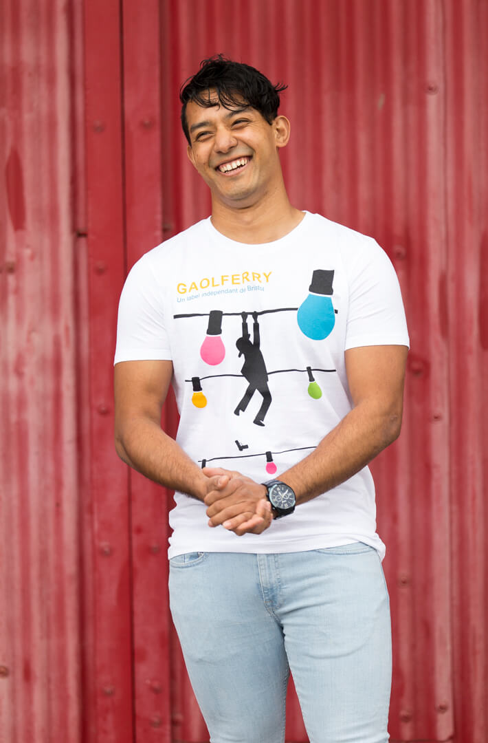 man wearing a white screen printed t-shirt against red background