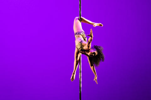 purple background with a women pole dancing at a competition