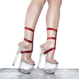 "The side view of a woman's feet in clear 8"" tall heels with 3 straps of glitter elastic around her ankles and shoes"