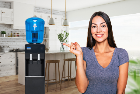 Six simple ways to drink more water. Young woman standing in modern kitchen smiling and pointing at her trusty water cooler.