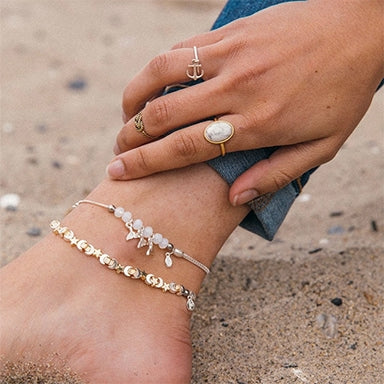 Woman wearing two ALEX AND ANI anklets