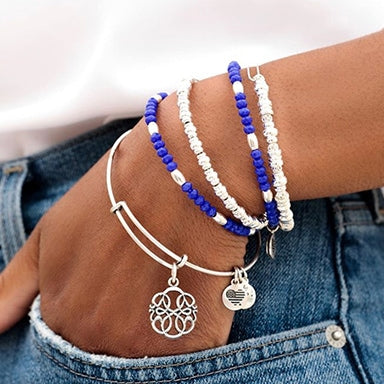 Woman wearing several ALEX AND ANI bracelets