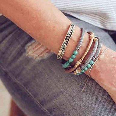 Woman wearing various ALEX AND ANI cuffs and wraps