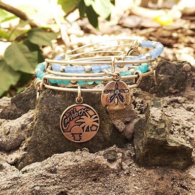 Two ALEX AND ANI bracelets sitting on a rock