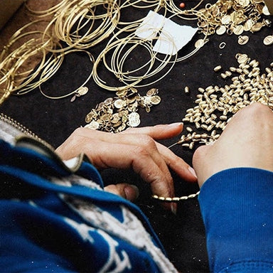 Woman constructing ALEX AND ANI bracelets