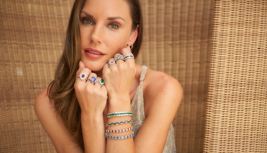 Woman wearing gemstone rings, bracelets, and earrings