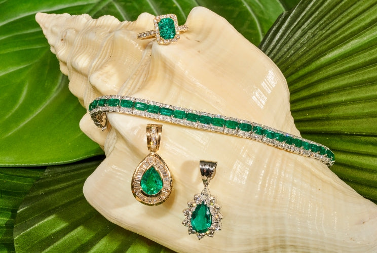 Emerald rings, earrings, and necklaces sitting on a conch shell