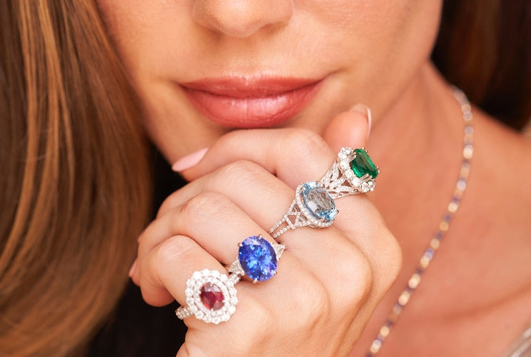 Woman wearring various gemstone rings and necklaces