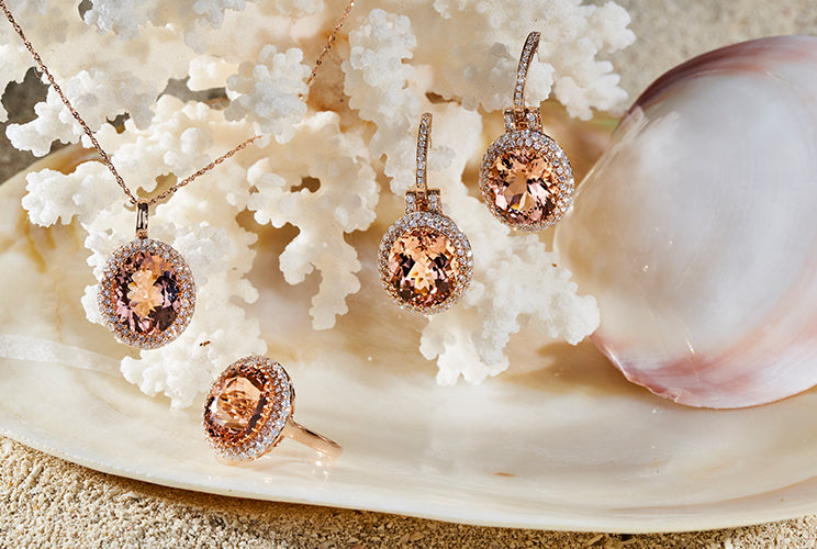 Morganite earrings, necklaces, and rings sitting on coral and shells