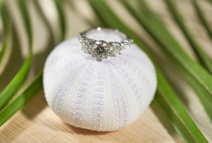 Engagement ring sitting on a pincushion