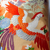Detail of flying bird embroidery in orange and silver silk