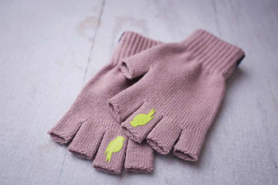Two Pink Fingerless Gloves with a Lime colored bird on the middle finger stacked