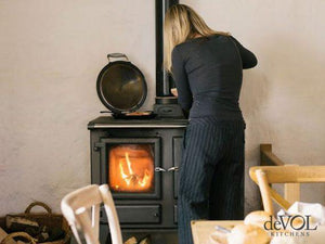 Esse Iroonheart Wood Burning Cooker In Kitchen with Woman Cooking Food and Placing Food on Hot Plate Beside Wooden Table and Chairs