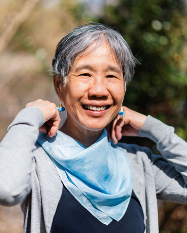 Asian woman with short salt and pepper hair, dark shirt and gray cardigan and sky blue crystal drop earrings, putting on sky blue silk bandana and smiling