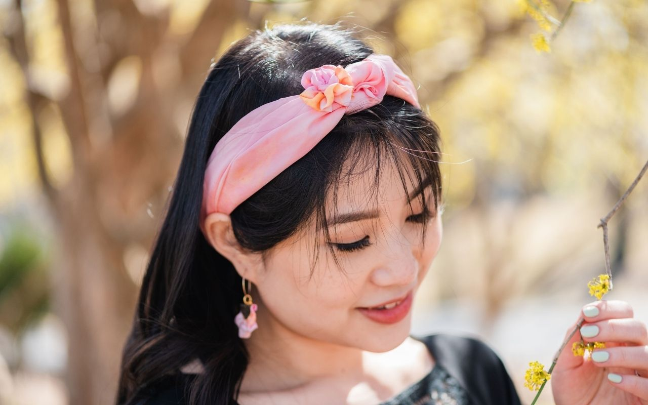 Chinese young woman with long dark hair looking down at a flowering branch in her hand, wearing silk scarf, magnetic full bloom brooch and lily hoop earrings in shell pink