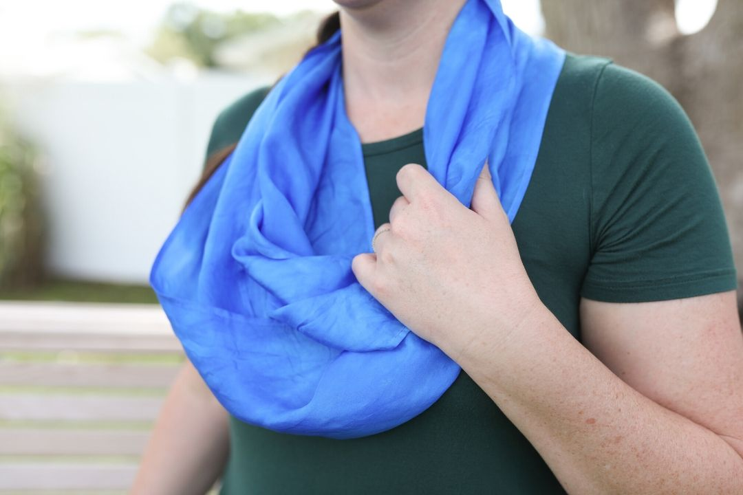 Close up of white woman wearing blue silk infinity scarf