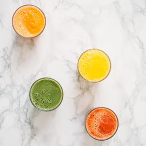 Green, orange, yellow juice in glasses on countertop.