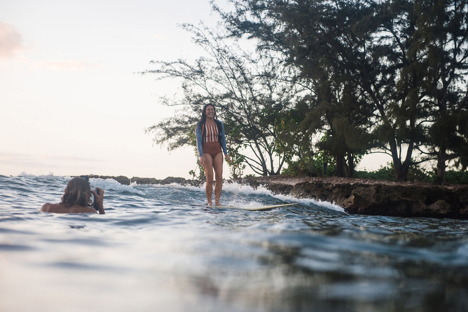 Keoki Saguibo and Rosie during a sunset surf session.