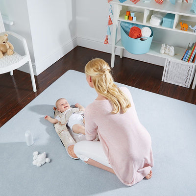 Mom kneeling on The Wriggler changing mat stopping toddler rolling over at nappy changing time