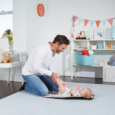 A baby in The Wriggler changing mat with a dad kneeling on the kneepads to stop rolling over at nappy changes