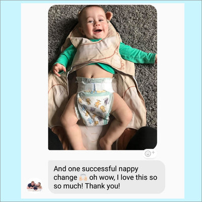 Review of toddler in The Wriggler portable changing mat smiling while mom kneels on the kneepads for an easy nappy change