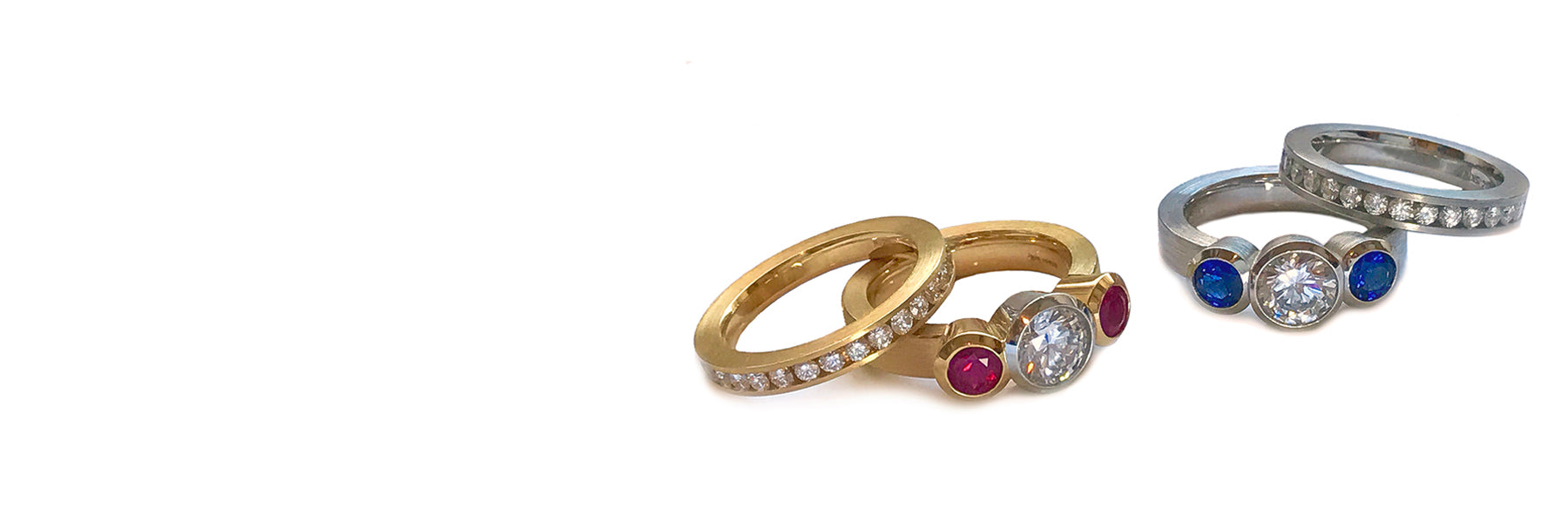 3 stone engagement rings with channel set wedding bands in 18k with rubies or Pt. with blue sapphires, both with diamonds.