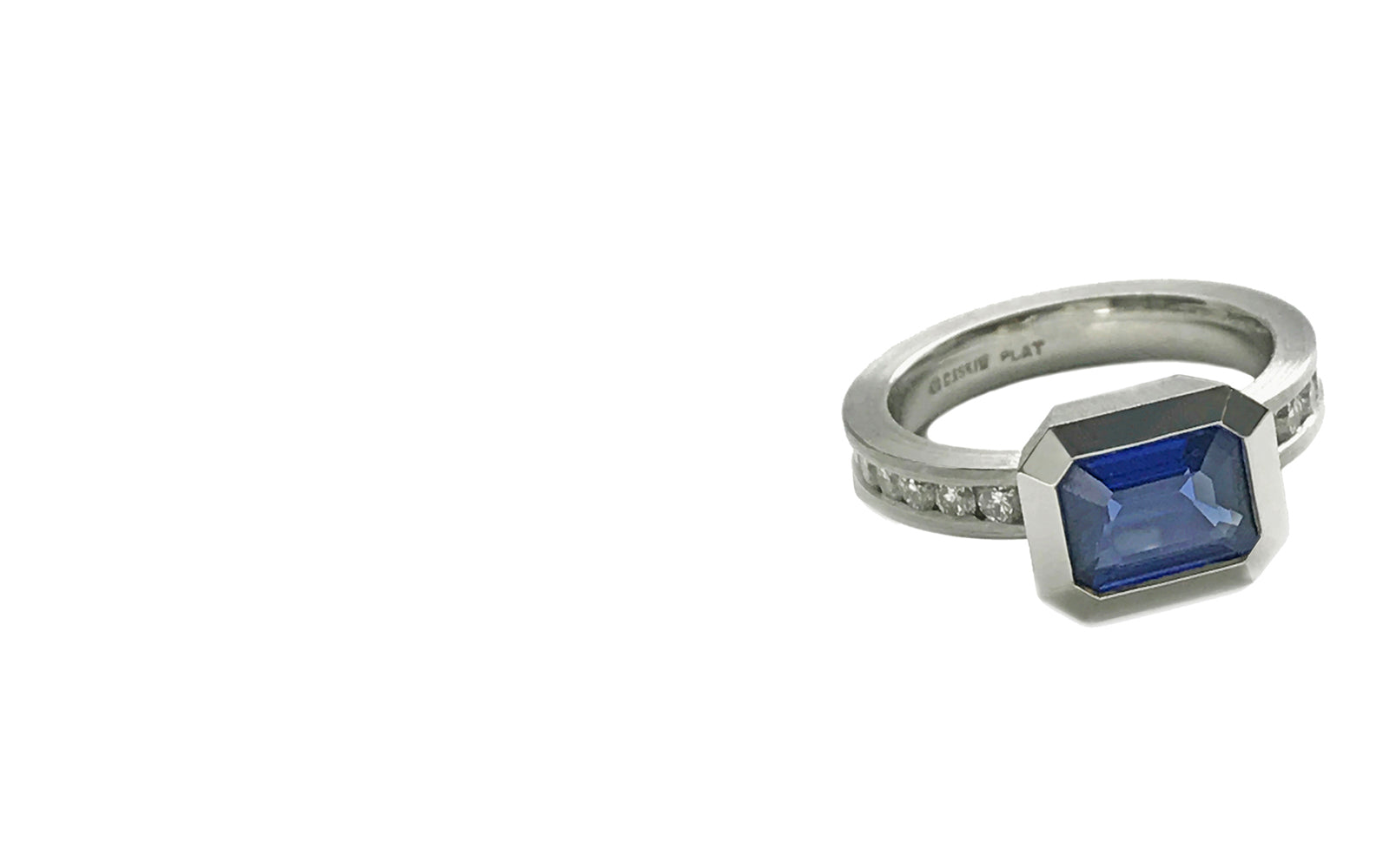 This deep blue 8 x 6mm, emerald cut sapphire is bezel set in platinum with a 3.4mm wide shank channel set with 14 round diamonds weighing .50tcw.