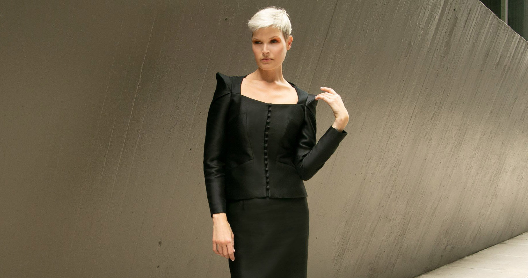 Model with short blond hair hearing black structured Jennifer Ritz jacket and fitted skirt.