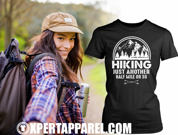 "Woman Taking selfie as she goes 'Hiking"" Black T-shirt mock-up off to the side with ""Hiking, just another half mile or so"" design on the front. available from the Xpert Apparel Store."