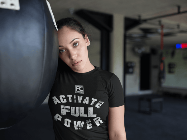 Female in the Gym  working out taking a break wearing a black t-shirt with grunge Activate Full Power design available from the Xpert Apparel Store