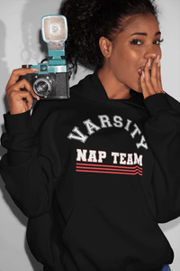 African American woman holding camera with hand over mouth wearing a black hoodie sweatshirt with Varsity Nap Team design on the front, available from the Xpert Apparel Store.