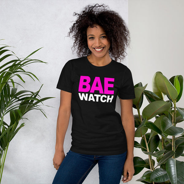 "Woman Poseing in front of potted plants in black T-shirt with ""Bae Watch"" design from the Xpert Apparel Store"