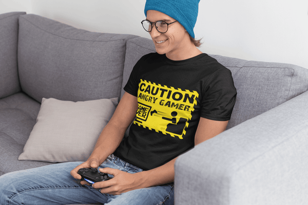 Guy sitting on couch playing video games wearing a black T-shirt with Caution Angry Gamer on the Front, now available from the Xpert Apparel Store