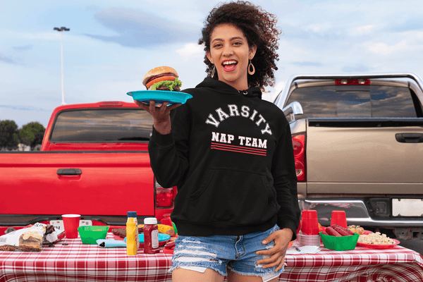 Woman at tailgate party holding plate with cheese burger wearing short blue jeans and black hoodie sweatshirt with Varsity Nap Team design on the front , available from the Xpert Apparel Store.