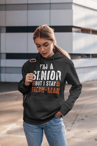 Girl standing at bus stop with backpack  wearing black Hoodie with I'm a Senior But I Stay Fresh-man T-shirt design from the Xpert Apparel Store