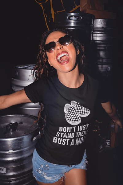 Lady having fun in a brewery, kegs of beer behind her, wearing a Don't just stand there bust a move Black T-shirt