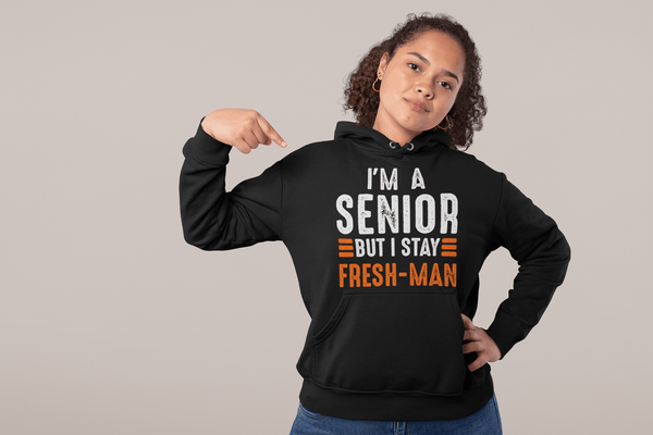 Girl  wearing black Hoodie pointing at the  I'm a Senior But I Stay Fresh-man T-shirt design from the Xpert Apparel Store