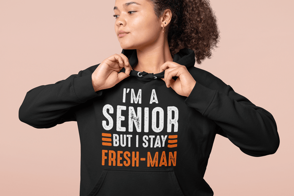 Girl fixing her collar  wearing black Hoodie wearing I'm a Senior But I Stay Fresh-man T-shirt design from the Xpert Apparel Store