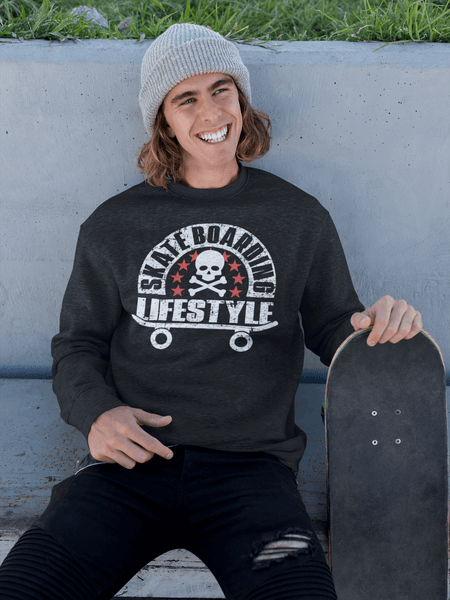 "Young man sitting on side walk with his skateboard by his side wearing black t-shirt/Sweater with ""Skateboarding Lifestyle"" design on the front available from the Xpert Apparel Store."