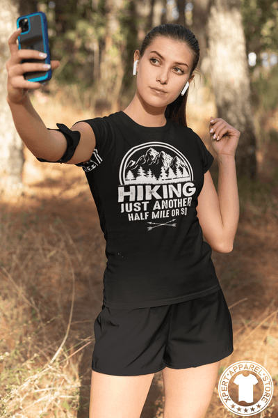 "Young Lady hiking in the woods stoped to take a selfie wearing a Black T-shirt with ""Hiking, just another half mile or so"" design on the front. available from the Xpert Apparel Store."